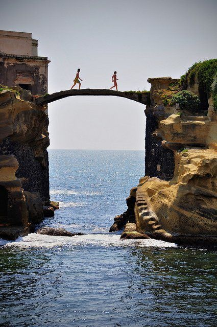 People Crossing Bridge Between Cliffs